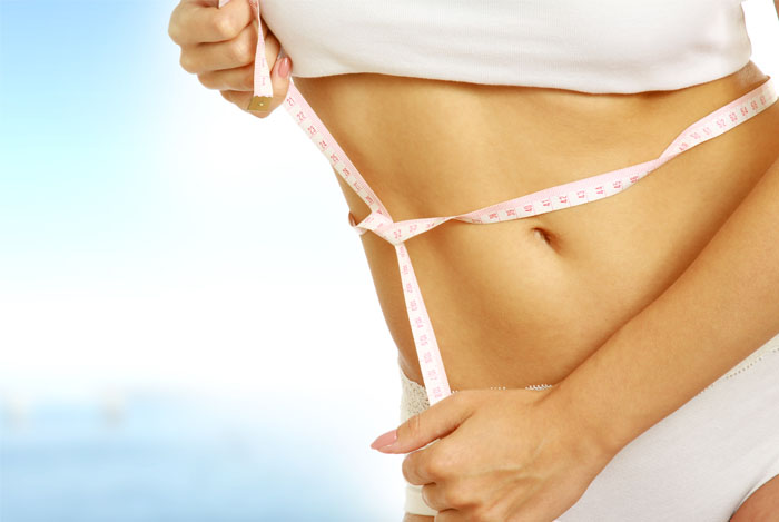 slim women measuring waist